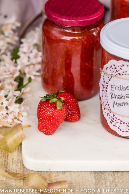 Ein Glas Erdbeer-Rhabarber-Fruchtaufstrich selbstgemacht mit einer Erdbeere