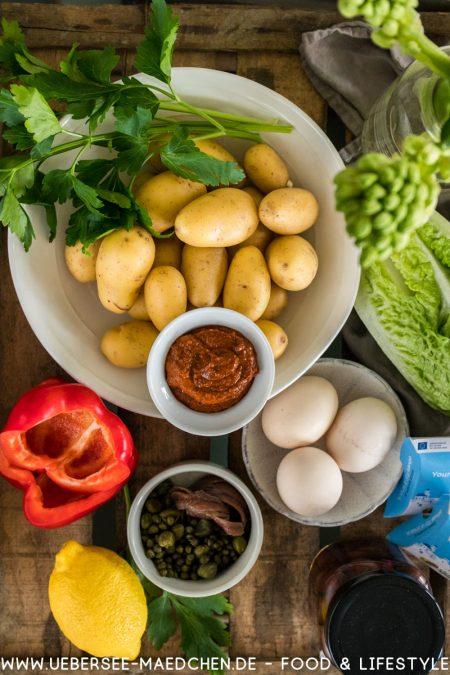 Zutaten für orientalischer Kartoffelsalat wie in Jerusalem von oben mit Harissa Kartoffeln Eiern Paprika Sardellen Kapern Romanasalat Oliven