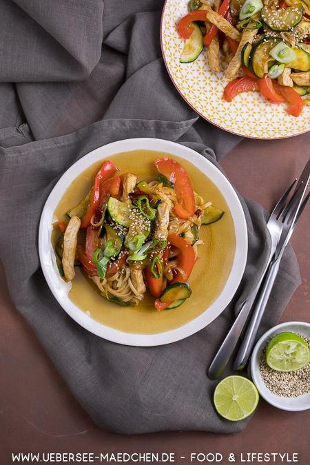 Zwei Teller Reisnudeln mit Gemüse und Schweinefleisch in Teriyaki-Sauce