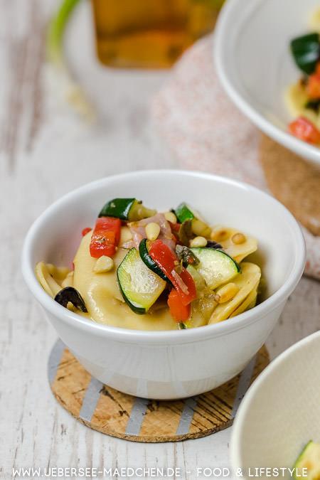 Eine Schüssel Ravioli-Salat mit Serrano-Schinken Paprika Zucchini Oliven Kapern Rezept von ÜberSee-Mädchen Foodblog vom Bodensee