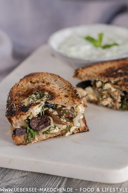 Ein Stück Sauerteigbrot mit vegetarisch griechischem Belag